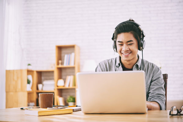 student on a computer wearing headphones - Orders
